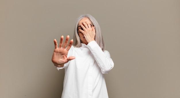 손으로 얼굴을 가리고 카메라를 멈추기 위해 다른 손을 앞으로 내밀고 사진이나 사진을 거부하는 노인 여성