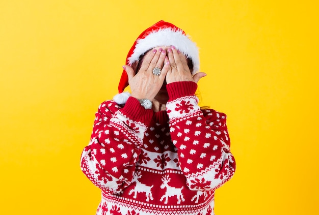 Senior woman covers her face with her hands, wearing santa calus hat