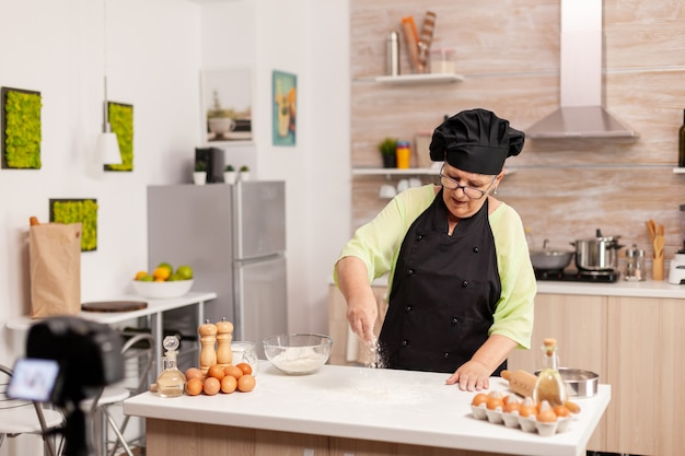 Старшая женщина, создающая контент для кулинарного блога, готовит вкусный хлеб. блогер на пенсии, повар, влиятельный человек, используя интернет-технологии, общается, ведет блог в социальных сетях с помощью цифрового оборудования.