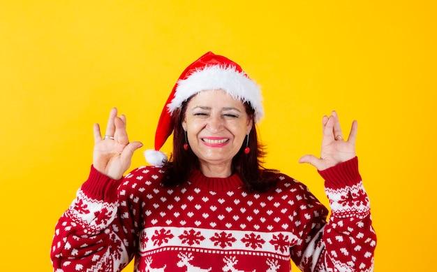 Senior woman crosses fingers, wearing santa claus hat