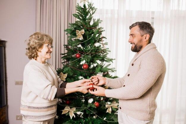 Старшая женщина украшает дерево с сыном
