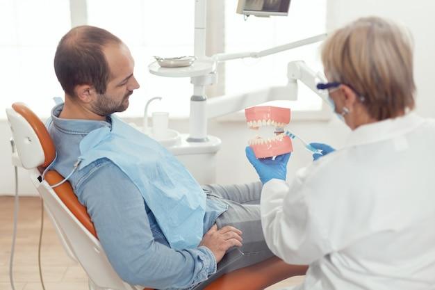 下顎の石膏モデルを使用して歯の手術を説明する年配の女性歯科医