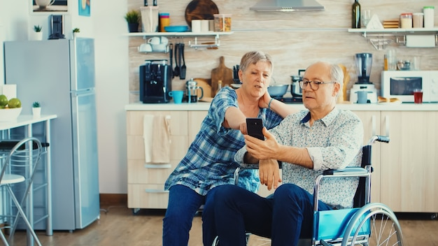 Senior woman and disabled husband in wheelchair surfing on internet using smartphone in kitchen. paralysied handicapped old elderly man using modern communication techonolgy.