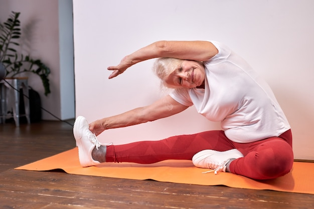 Старшая женщина занимается спортом дома на полу, красивая здоровая женщина растягивает руки и ноги, занимается йогой, ведет здоровый образ жизни