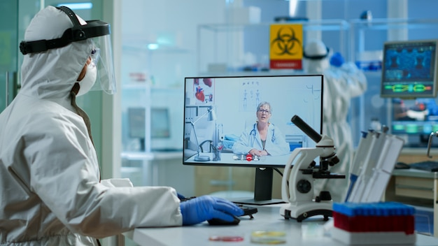 Senior woman doctor offering medical online advices to chemist in ppe suit using pc webcam. scientist showing blood sample during online discussion, researching treatment against covid19 virus