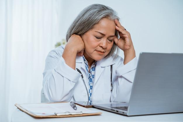 Senior woman doctor using laptop