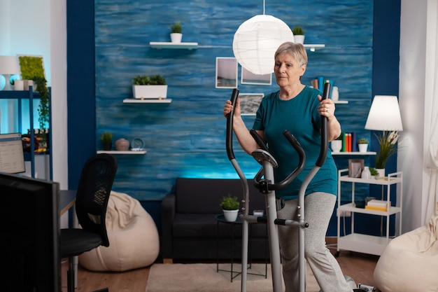 Senior woman doing aerobics on cycling bike machine in living room for well being