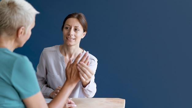 복사 공간이 있는 심리학자와 작업 치료 세션을 하는 수석 여성