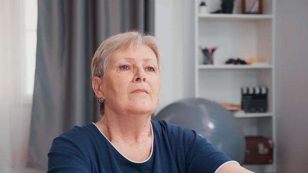 居間で瞑想しながら呼吸運動をしている年配の女性。老人年金受給者の定年での在宅スポーツ活動での運動トレーニング
