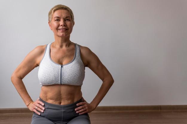 Старшая женщина делает упражнения в помещении