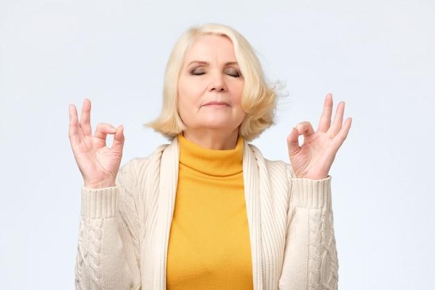 指で瞑想のジェスチャーをしている年配の女性