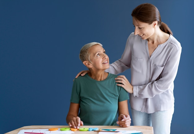 Senior woman doing an occupational therapy session with a psychologist with copy space