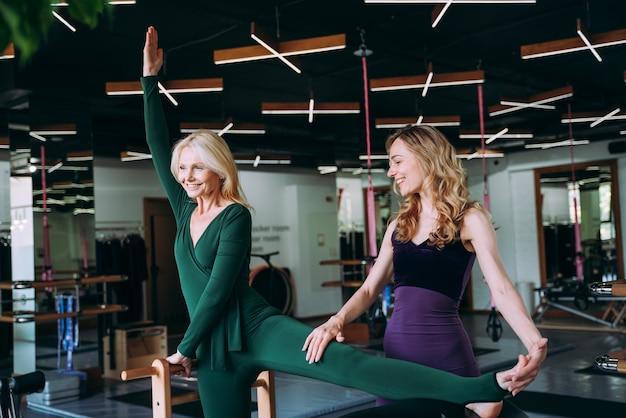 スポーツセンターでコーチと一緒に物理的なリハビリとピラティスをしている年配の女性