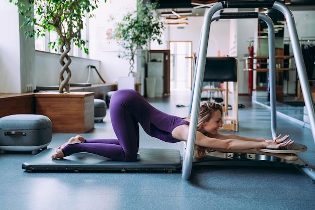 스포츠 센터에서 코치와 함께 신체 재활과 필라테스를 하는 시니어 여성