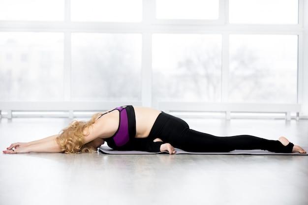 Senior donna facendo sleeping swan posa di yoga