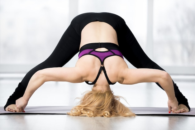 Senior woman doing standing straddle forward bend yoga pose