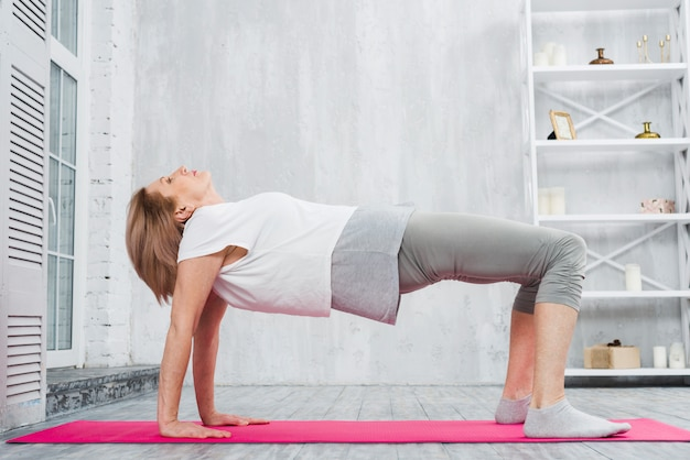 Senior woman doing stretching exercise over pink mat at home