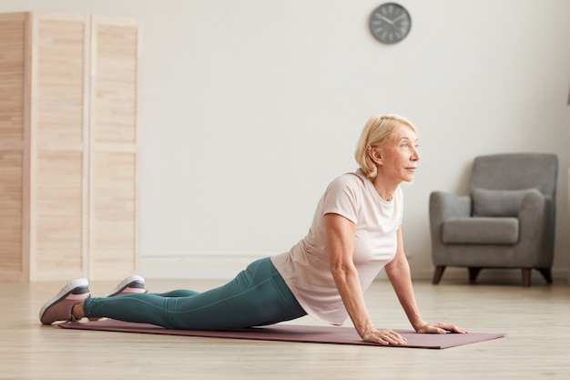 Senior woman doing stretching exercises on the floor in the room at home