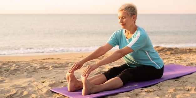 Donna maggiore che fa yoga sulla spiaggia