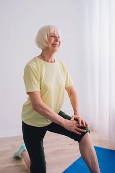 屋内でヨガをしている年配の女性アンチエイジスポーツヨガの概念 Premium写真