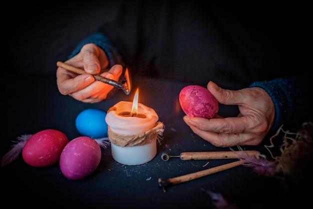 特別なスタイラスとキャンドルライト、黒い表面上の暗いスタイルの代替イースター、春の休日のコンセプトで伝統的なウクライナの書かれたワックスの方法で卵を描く年配の女性