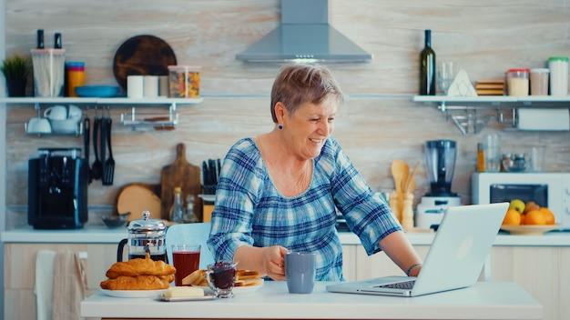 朝食をとりながらキッチンで家族とのビデオ会議中にコーヒーを飲み、手を振る年配の女性。インターネットオンラインチャット技術を使用している高齢者ビデオウェブカメラがビデオ通話を行っているc