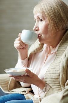 カフェでコーヒーを飲む年配の女性