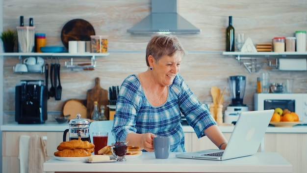 Senior woman drinking coffee and waving during a video conference with family in kitchen while having breakfast. elderly person using internet online chat technology video webcam making a video call c
