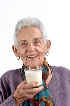 Senior woman drinking milk on white background