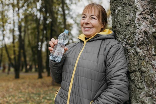 Старшая женщина пьет воду после тренировки на природе