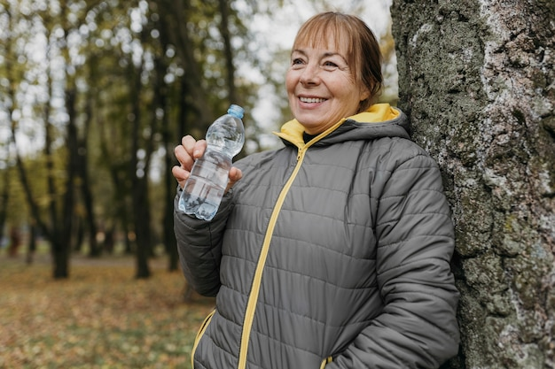 Senior woman drinking water after working out in nature