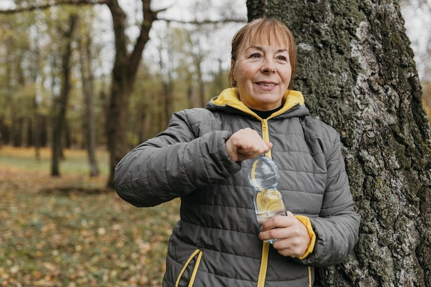 Старшая женщина пьет воду после тренировки на открытом воздухе
