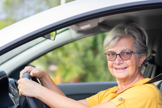 Senior woman driving a car in the city. portrait of attractive elderly woman looking out of the window and smiling