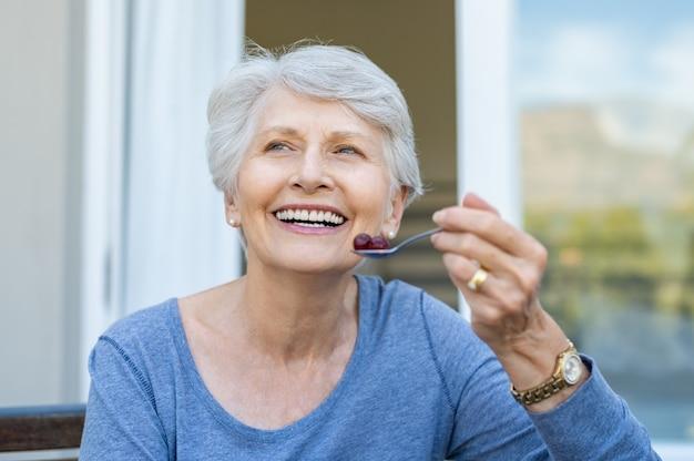 果物を食べる年配の女性