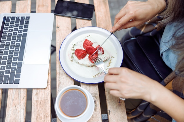 Senior woman eats delicious toast with strawberries and cream near laptop at table outdoors