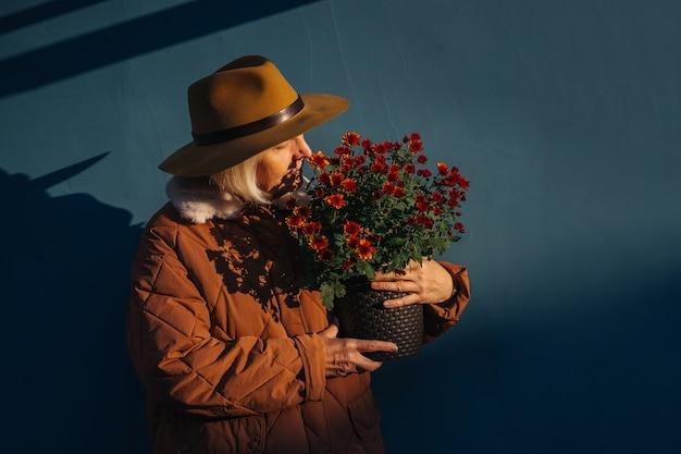Старшая женщина наслаждается ароматом цветов. пожилая женщина несет горшок с цветами в солнечный летний день