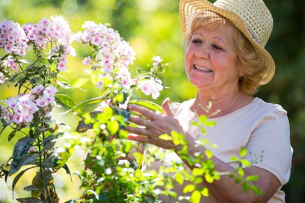 年配の女性が庭で花を調べる