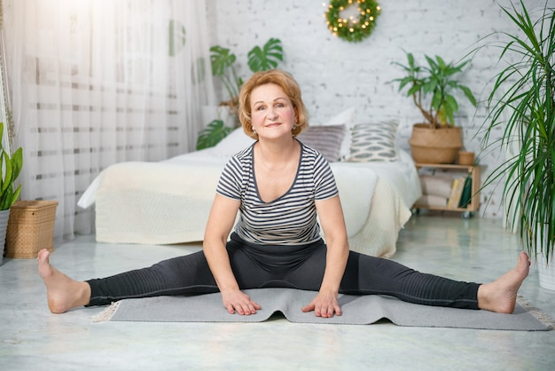 Senior woman exercising home, the concept of a healthy lifestyle, fitness and yoga