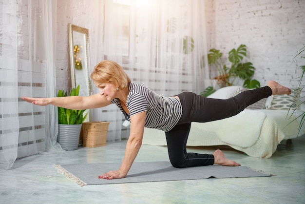 Senior woman exercising home, the concept of a healthy lifestyle, fitness and yoga.