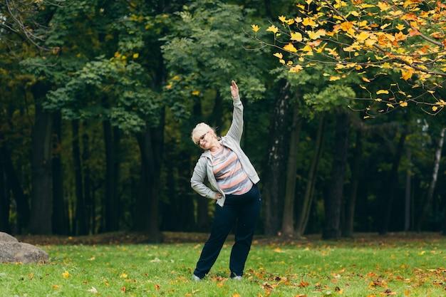 Старшая женщина, тренирующаяся в парке