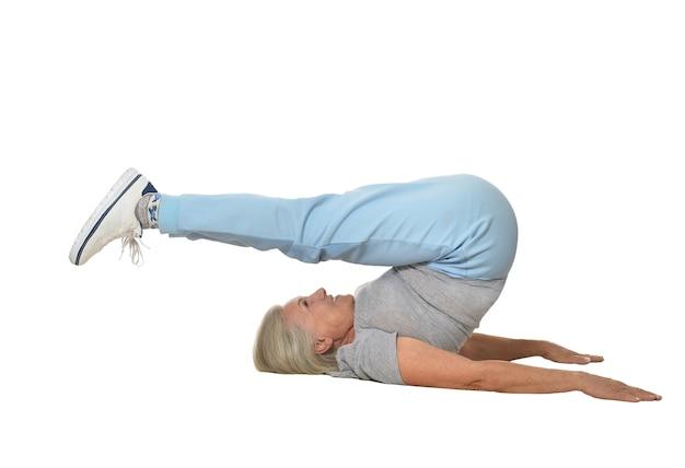 Старшая женщина, тренирующаяся на белом фоне