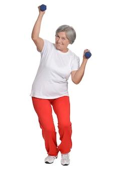 白い背景の上のダンベルで運動する年配の女性