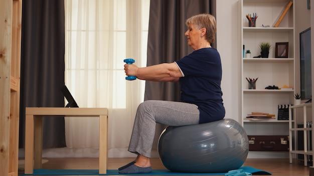 タブレットコンピュータでオンラインレッスンを見ているダンベルで運動している年配の女性。オンライントレーニング学習技術老婆リフティングトレーニング健康的なライフスタイルスポーツフィットネストレーニング自宅で私たちと一緒に