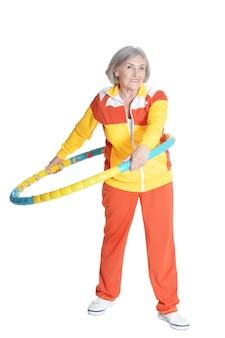 白い背景の上のフープで運動する年配の女性