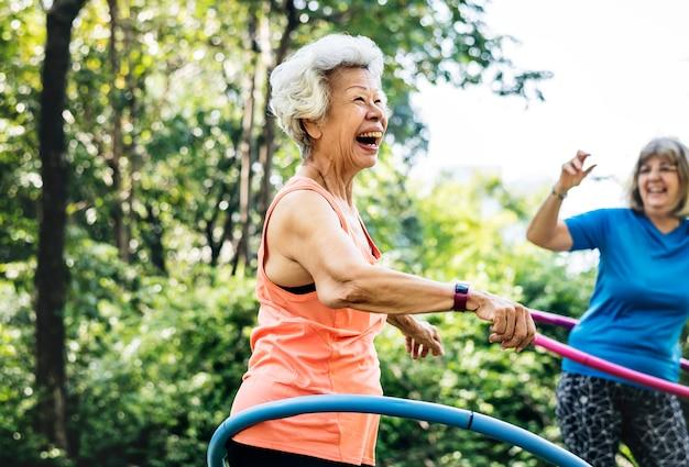 Senior woman exercising with a hula hoop
