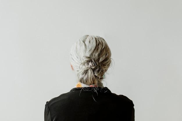 Senior woman facing a gray wall
