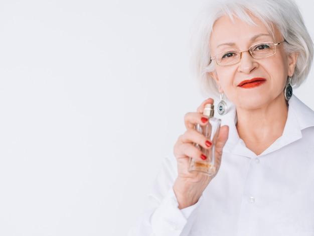 年配の女性のファッションスタイル。香水のトレンド。女性の手に高価な香りのボトル。