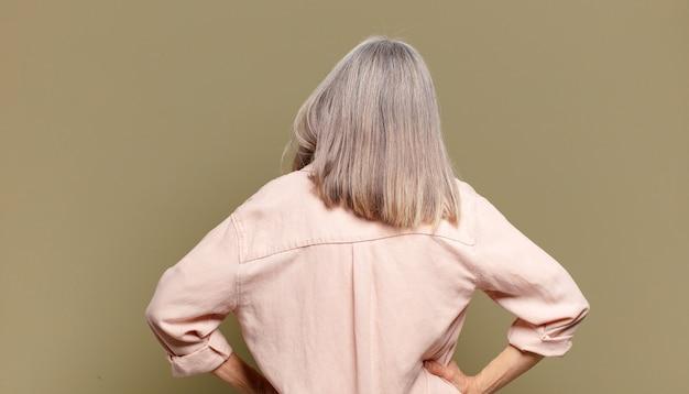 혼란 스럽거나 가득 차 있거나 의심과 질문을 느끼는 노인 여성, 엉덩이에 손, 후면보기