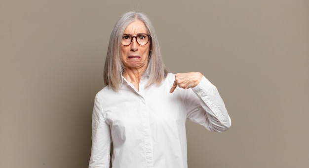 Senior woman feeling confused, puzzled and insecure, pointing to self wondering and asking who, me?