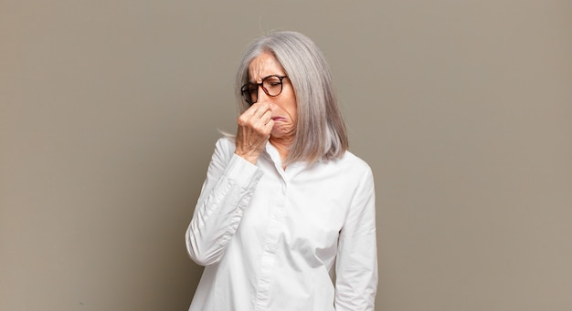 Senior woman feeling disgusted, holding nose to avoid smelling a foul and unpleasant stench
